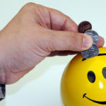Caucasion hand and arm dressed in military camouflage placing coins in a yellow piggy bank