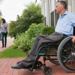 Middle aged caucasian male in wheelchair exiting door